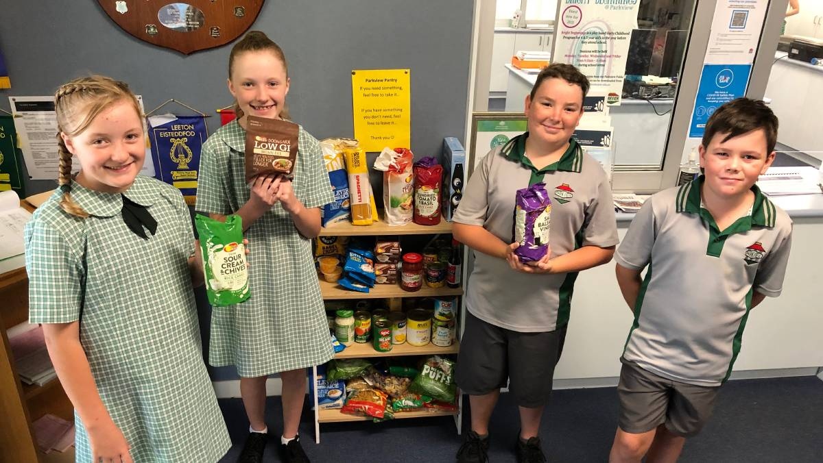 HELP: Students (from left) Myah and Halle O'Meley, 11, Logan Stuart, 11, and Bailey Irvin with the school's community pantry. Photo: Talia Pattison